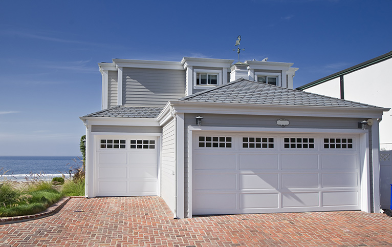 Grey and white beach house with double garage