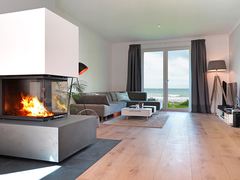 Modern interior with fireplace, wooden flooring and sea view