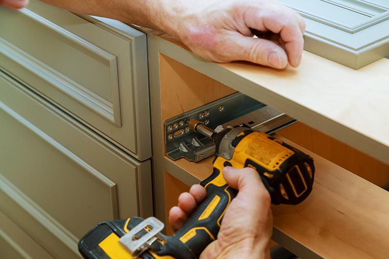Kitchen specialist assembling kitchen cupboard