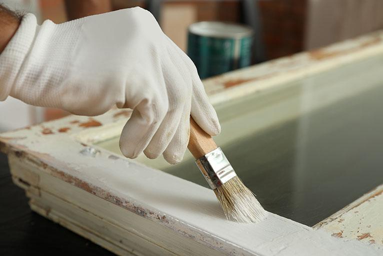 Repairman painting old window frame