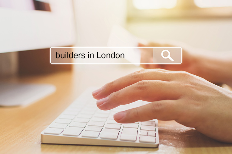 Person's hand hovering over computer keyboard - ready to search for 'builders in London'.