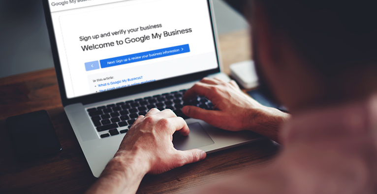 Man sat in front of open laptop with a screen that reads: 'Welcome to Google My Business'.