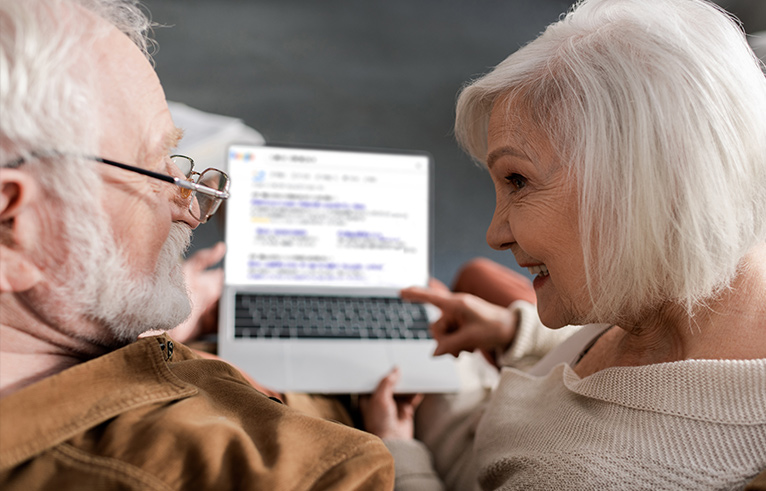 Elderly couple sat facing each other whilst holding an open laptop.