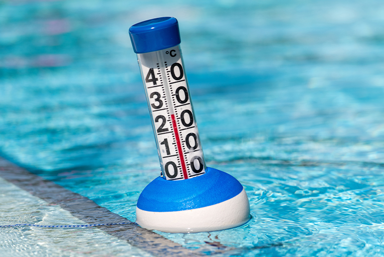 Close up of a thermometer, floating in a swimming pool.