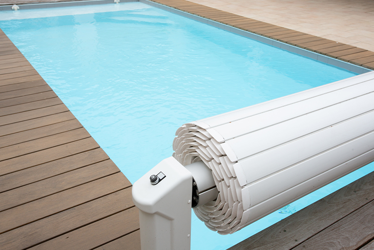 Pool cover fitted to one end of a rectangular swimming pool.