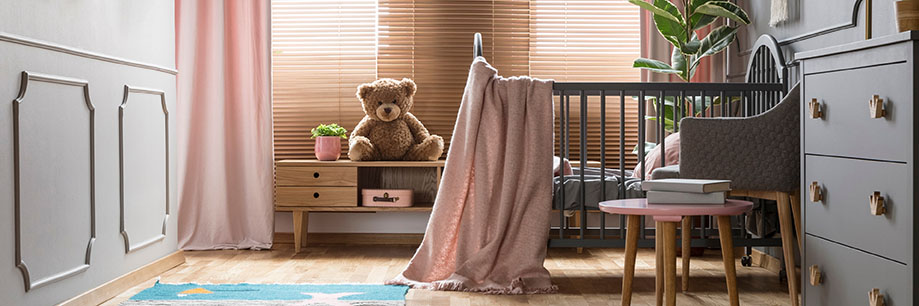 Nursery interior with wooden crib, grey furniture and pastel pink decorations