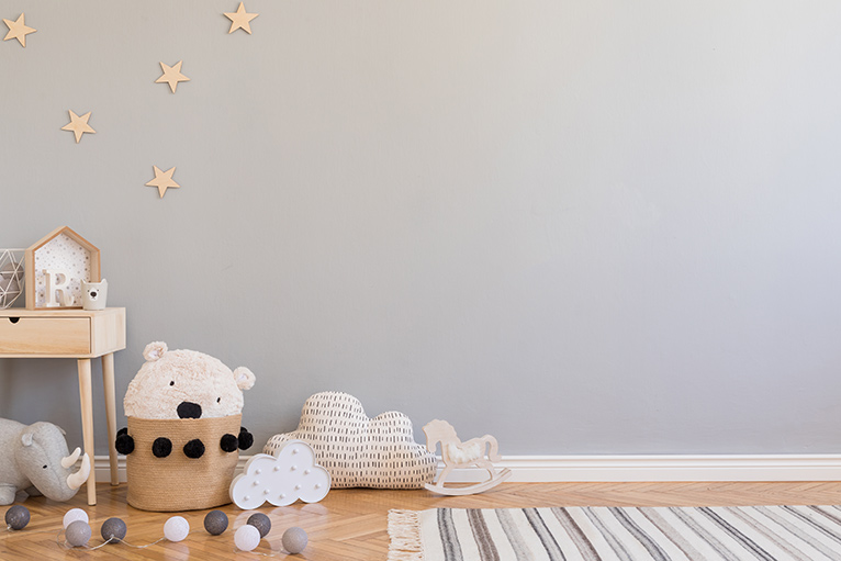 Scandinavian style nursery with light grey wall, wooden stars, natural toys and wooden furniture