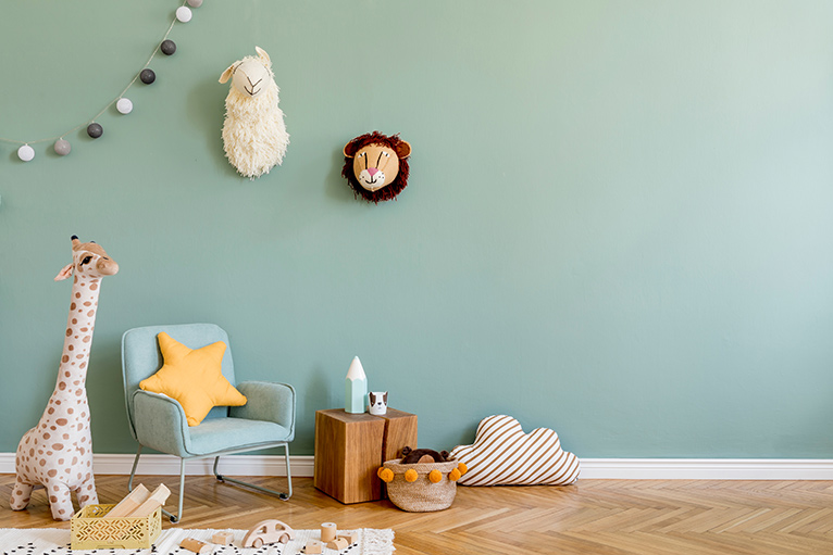 Nursery with muted green walls and soft animal toys