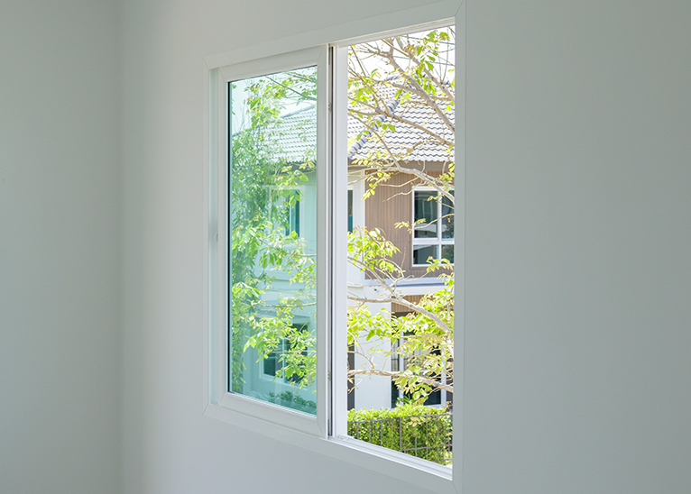 Slider window in house, looking out onto sunlit trees.
