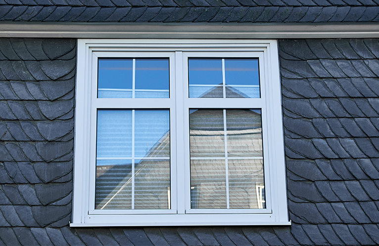 White casement window perched on the side of a house's roof.