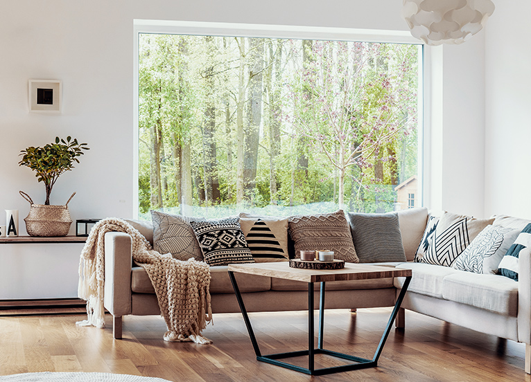 Large picture window, set back behind a couch in a modern home. Window shows wide view of forest trees.