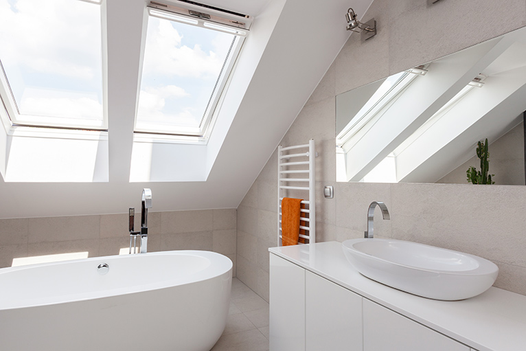 Skylight windows letting light into a white-painted, fresh modern bathroom.