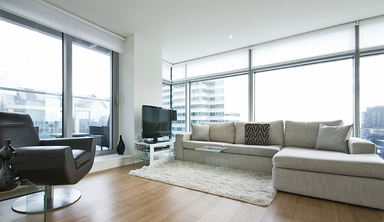 Tall and broad window walls, surrounding the living area of a flat in a high-rise building.