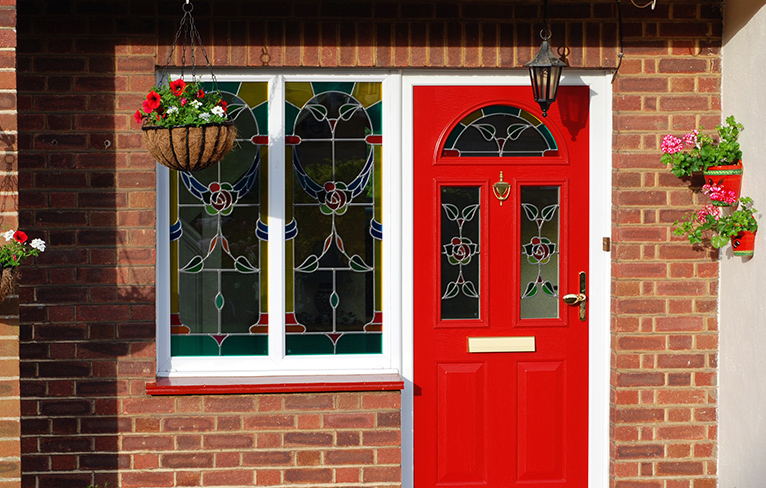 Colourful stained-glass windows with a blue and red rose design on the door and adjoining window of a house.