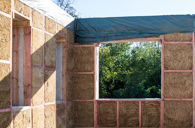 Building site showing walls of house, mid-construction, made of straw bales.