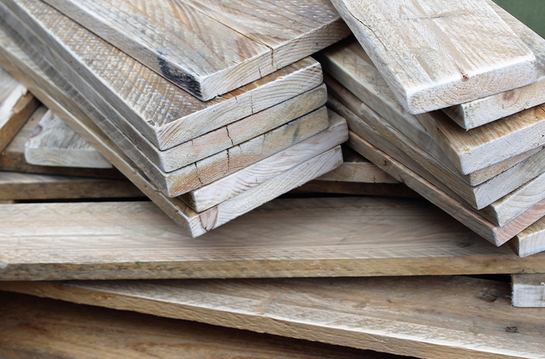 Light-coloured planks of reclaimed wood stacked in a messy pile.