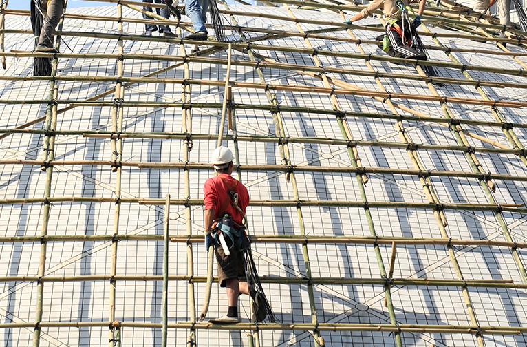 Tradesmen working on the roof of a building being constructed with bamboo.