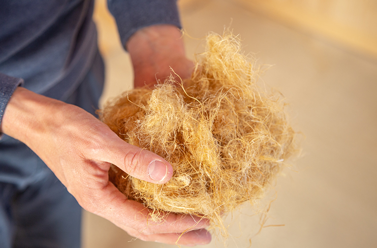 Man holding a bunch of sustainable fibres between his hands.